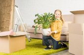 happy little child holding houseplant and smiling at camera while moving home