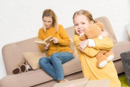 cute little girl hugging teddy bear and smiling at camera while mother reading book on sofa