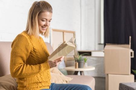 Photo pour Sourire jeune femme lecture livre tout en déménageant à la maison - image libre de droit