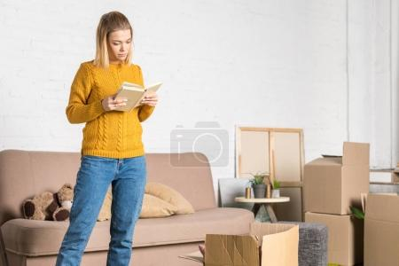 beautiful young woman reading book while moving home