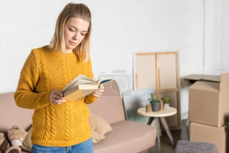 attractive young woman reading book while moving home