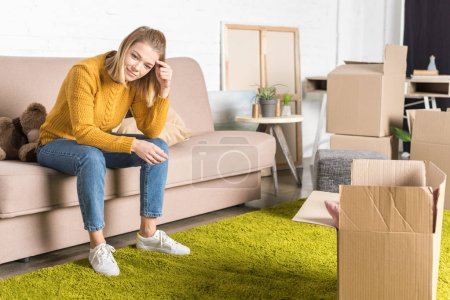 smiling young woman sitting on sofa while packing cardboard boxes during relocation