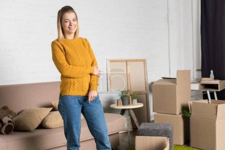 beautiful young woman smiling at camera while moving home