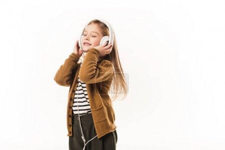 joyful little child listening music with headphones isolated on white