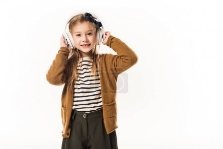 little child listening music with headphones and looking at camera isolated on white