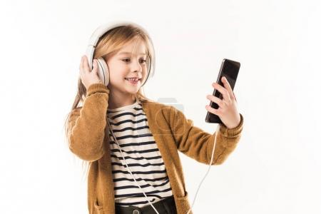 happy little child listening music with headphones and taking selfie isolated on white