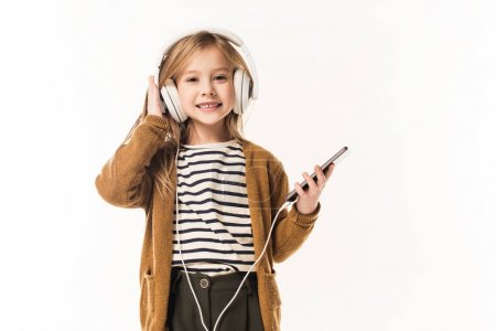 adorable little child listening music with headphones and smartphone isolated on white