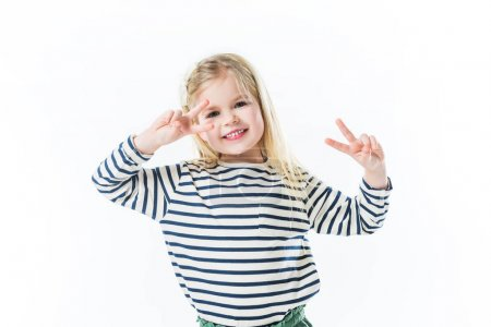 smiling little child dancing and making peace gestures with hands isolated on white