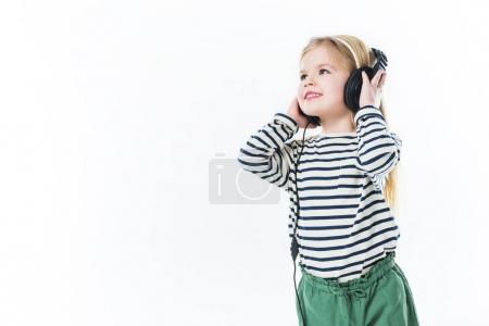 happy little child listening music with headphones isolated on white