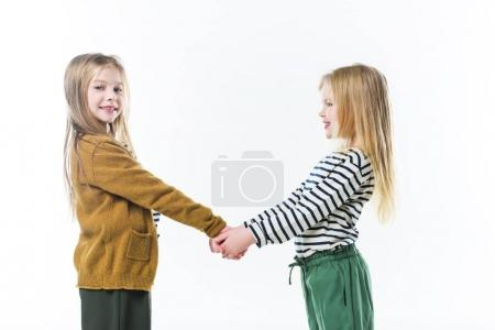 happy little sisters holding hands isolated on white