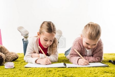 Photo for Focused little sisters drawing with color pencils together on floor isolated on white - Royalty Free Image