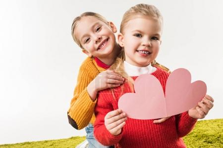 little sisters with pink carfboard heart for handmade greeting card isolated on white