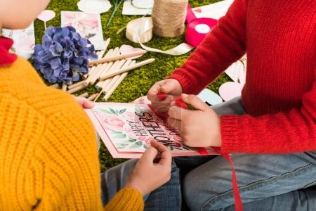 cropped shot of little kids preparing greeting card for mothers day