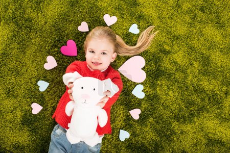 top view of happy little child surrounded with hearts lying on green soft carpet with toy rabbit