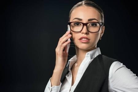 young confident businesswoman talking on smartphone, isolated on black