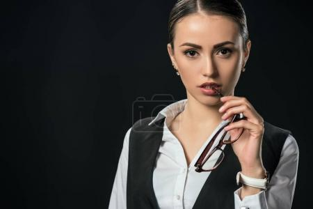 Photo for Young thoughtful businesswoman with eyeglasses, isolated on black - Royalty Free Image