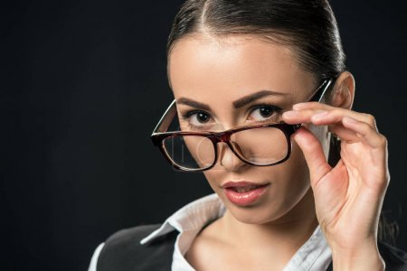 portrait of beautiful businesswoman in glasses looking at camera, isolated on black