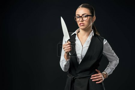 Photo for Young confident businesswoman holding knife, isolated on black - Royalty Free Image