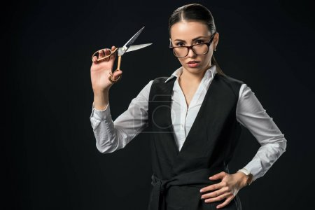 Photo for Young businesswoman holding scissors, isolated on black - Royalty Free Image