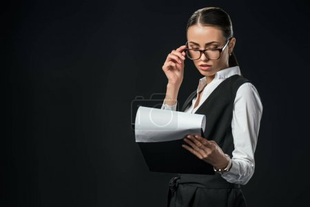 confident businesswoman holding documents on clipboard, isolated on black