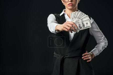 Photo for Cropped view of businesswoman holding dollar banknotes, isolated on black - Royalty Free Image