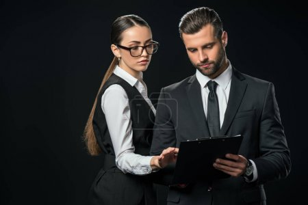 businesspeople doing paperwork together, isolated on black