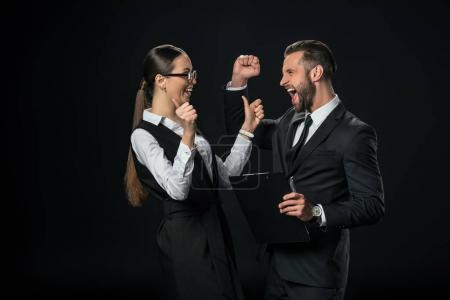 Photo for Excited businesspeople celebrating triumph, isolated on black - Royalty Free Image