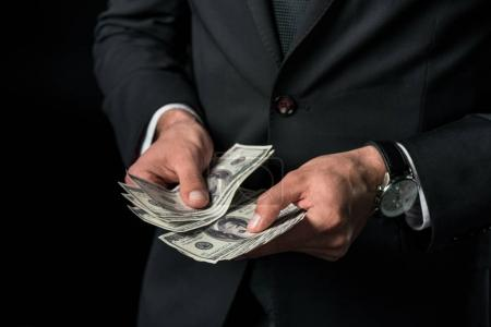 cropped view of businessman holding dollar banknotes, isolated on black