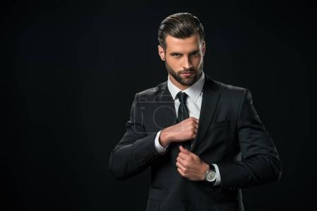 handsome businessman taking something from pocket of jacket, isolated on black