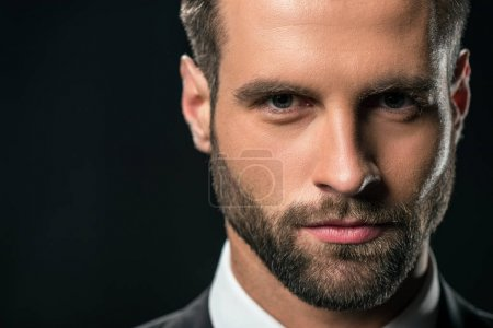 portrait of handsome businessman in jacket looking at camera, isolated on black