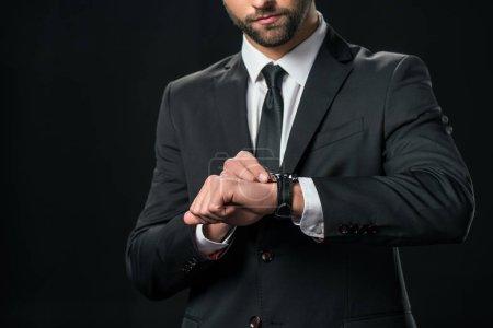Photo pour Vue recadrée de l'homme d'affaires en veste regardant montre-bracelet, isolé sur noir - image libre de droit