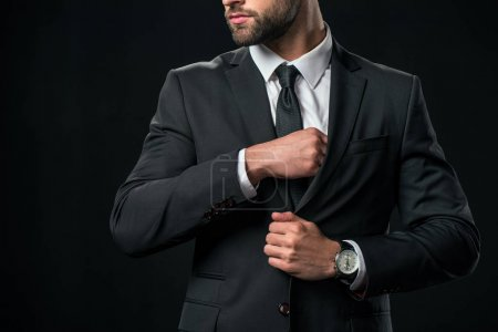 cropped view of businessman taking something from pocket of jacket, isolated on black