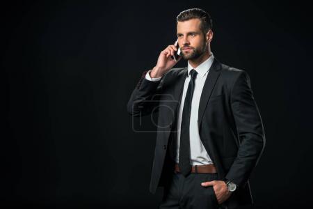 Photo pour Bel homme d'affaires en veste parler sur smartphone, isolée sur fond noir - image libre de droit
