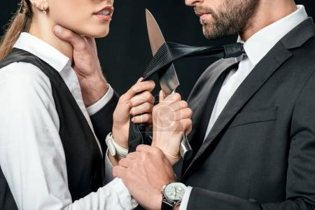 cropped view of businesspeople holding knife and quarreling isolated on black