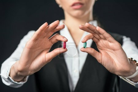 Photo for Cropped view of businesswoman holding blue and red pills, isolated on black - Royalty Free Image