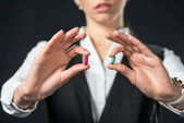 cropped view of businesswoman holding blue and red pills, isolated on black