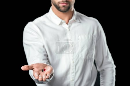 cropped view of businessman holding blue and red pills, isolated on black