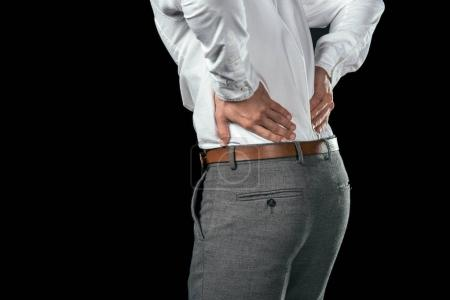 cropped view of businessman having pain in back, isolated on black