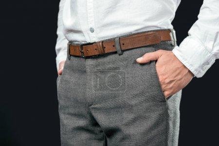 cropped view of businessman with hands in pockets, isolated on black