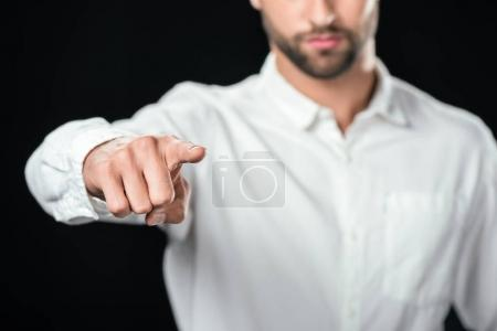cropped view of businessman in white shirt pointing at you, isolated on black