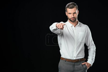 handsome businessman in white shirt pointing at you, isolated on black