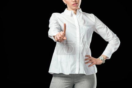 cropped view of businesswoman pointing up, isolated on black