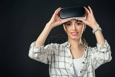 Photo pour Femme souriante utilisant casque de réalité virtuelle, isolé sur noir - image libre de droit