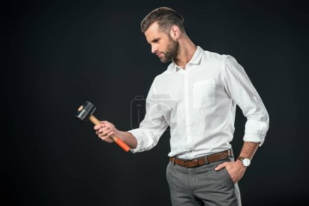 handsome businessman in white shirt holding hammer, isolated on black