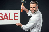 handsome man with hammer and sale sign, isolated on black