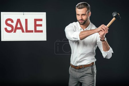 handsome businessman with hammer and sale sign, isolated on black