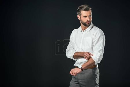 Photo pour Bel homme d'affaires en chemise blanche, isolée sur fond noir - image libre de droit