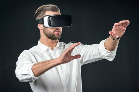 man gesturing and using virtual reality headset, isolated on black