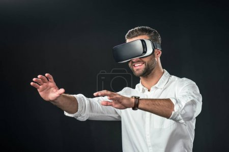 smiling man using virtual reality headset, isolated on black