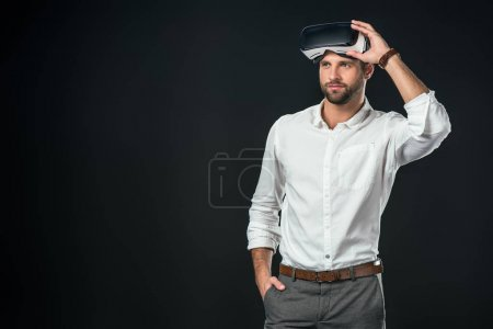 Photo for Handsome man using virtual reality headset, isolated on black - Royalty Free Image